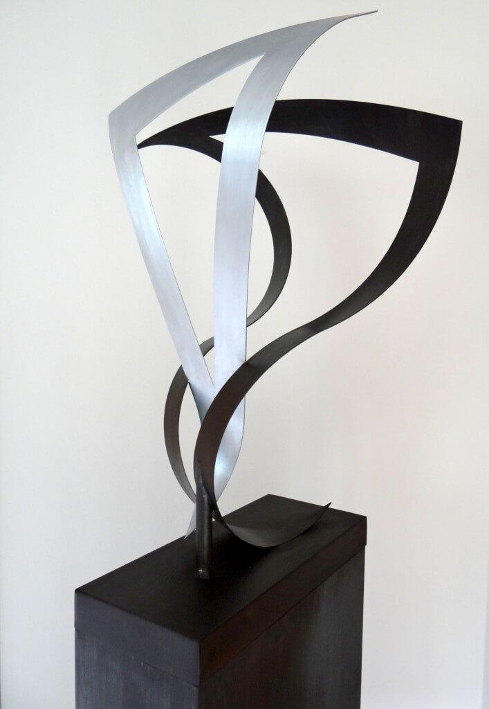 """""""Opstandigheid"""" symboliseert het rebellerende gedrag. Twee ongelijkzijdige driehoeken, Zink 20, afm. 45 x 60 x 80 cm."""