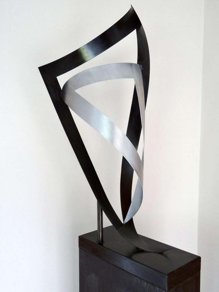 """""""Samen"""" symboliseert de verbondenheid. Twee ongelijkzijdige driehoeken, Zink 20, afm. 45 x 40 x 90 cm."""