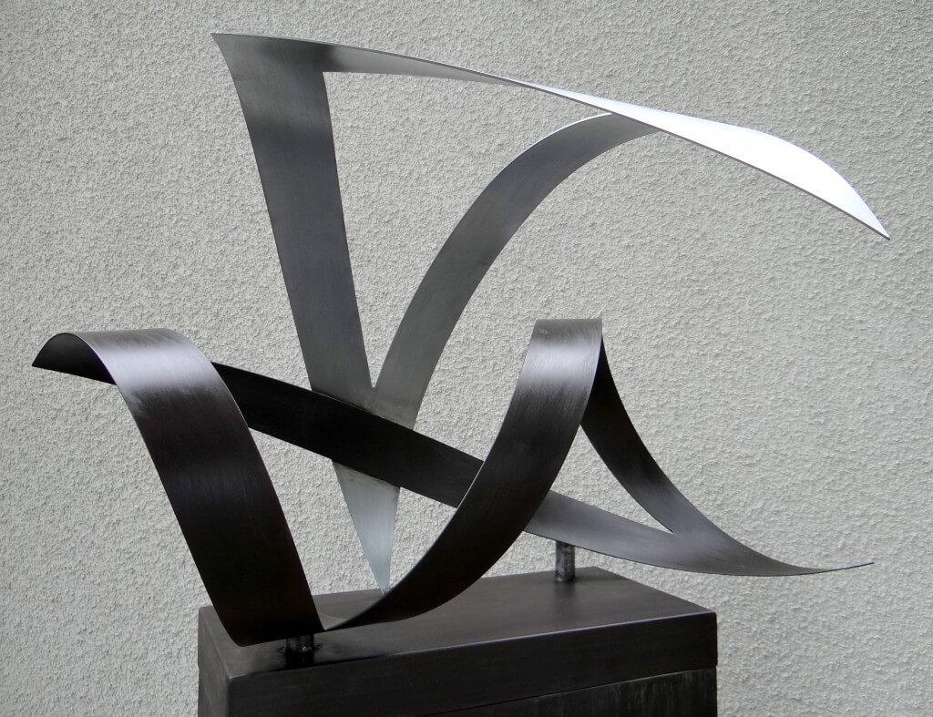 """""""Tijdelijkheid"""" symboliseert de vergankelijkheid. Twee ongelijkzijdige driehoeken, Zink 20, afm. 80 x 50 x 45 cm."""